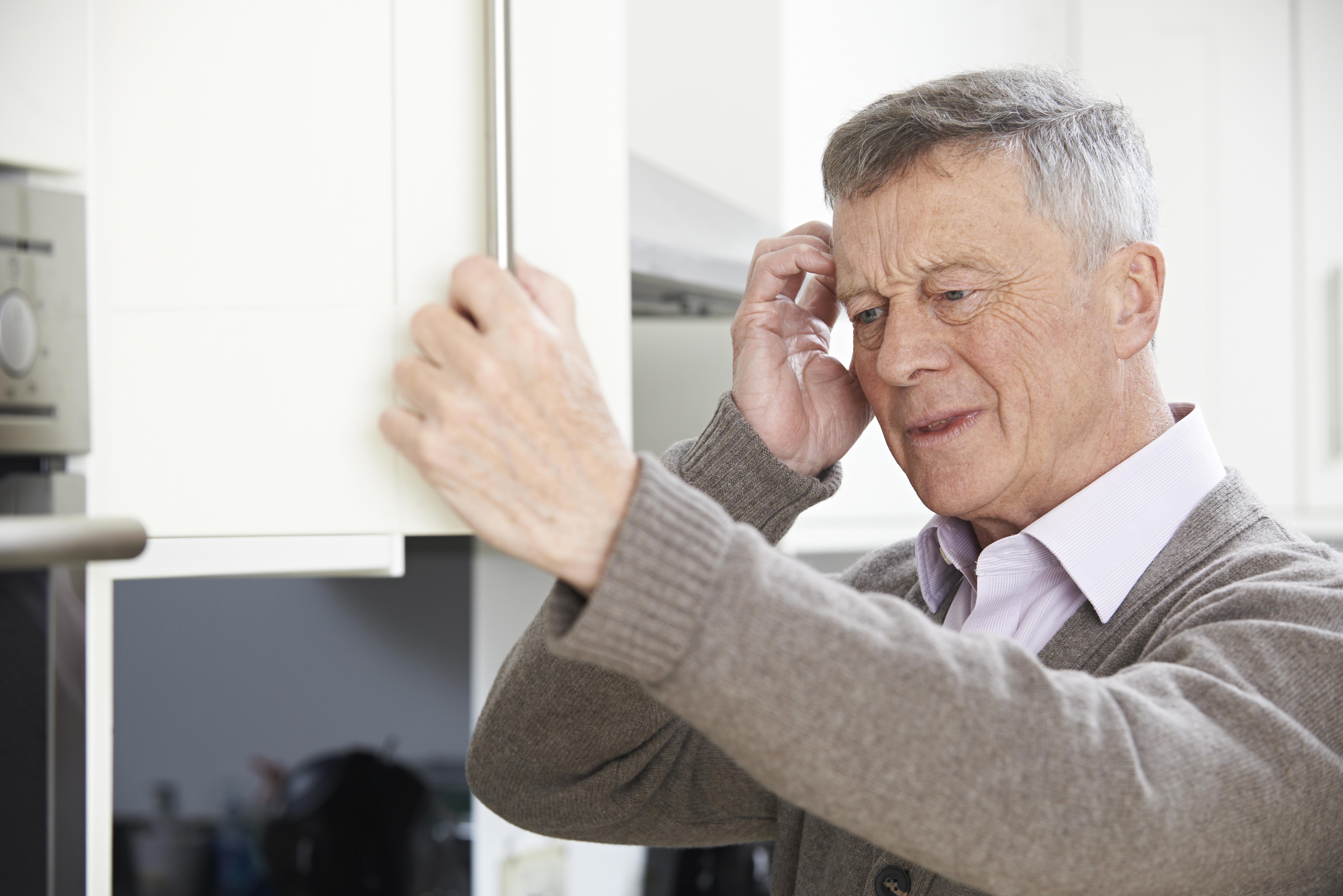Forgetful Senior Man Looking In Cupboard